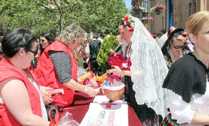Voluntario de Cruz Roja recogen los alimentos y los productos de limpieza aportados por los participantes en la procesión.